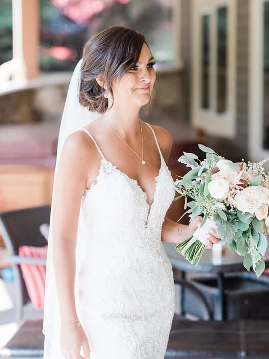 Bride wearing a white lace bridal gown and holding her dusty rose and blush bridal bouquet featuring white o'hara garden roses, white ranunculus, amnesia roses, babies breath, astilbe, spray roses, rose gold painted scabiosa pods and quicksand roses with dusty miller and eucalyptus greenery.