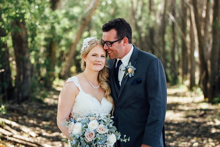 Kelsie and Kyle's blush and blue vintage barn wedding - Kelsie holding bouquet made of quicksand roses, white o'hara garden roses, gypsophila, delphiniums and a mixed variety of eucalyptus greenery; Kyle wearing a boutonniere made of a blush rose accented by blue delphinium, babies breath and eucalyptus.
