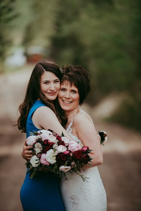 Bride hugging daughter holding a pink and burgundy bridal bouquet featuring burgundy helleborus, Sarah Bernhardt peonies, Blush and White ranunculus, black baccara roses, blackberry scoop scabiosa, burgundy tulips and accented with pale pink astrantia and seeded eucalyptus greenery.