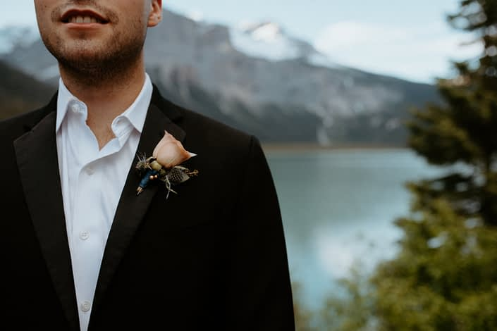 Blush peach boutonniere with a touch of eryngium and eucalyptus greenery