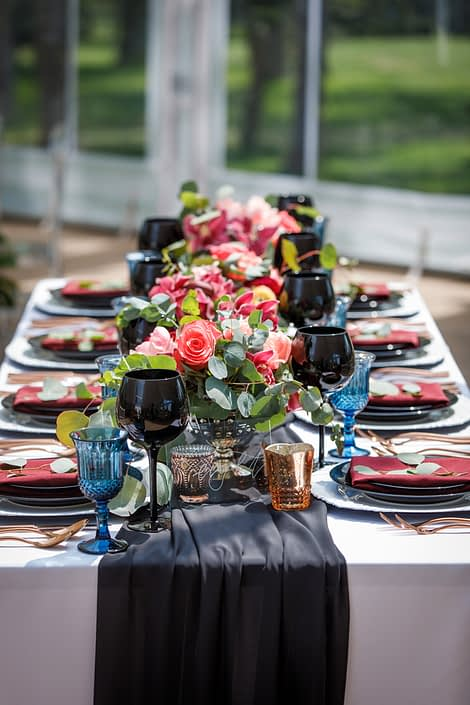 rectangular table with black table runner and wine glasses and three compote style centerpieces in coral and burgundy