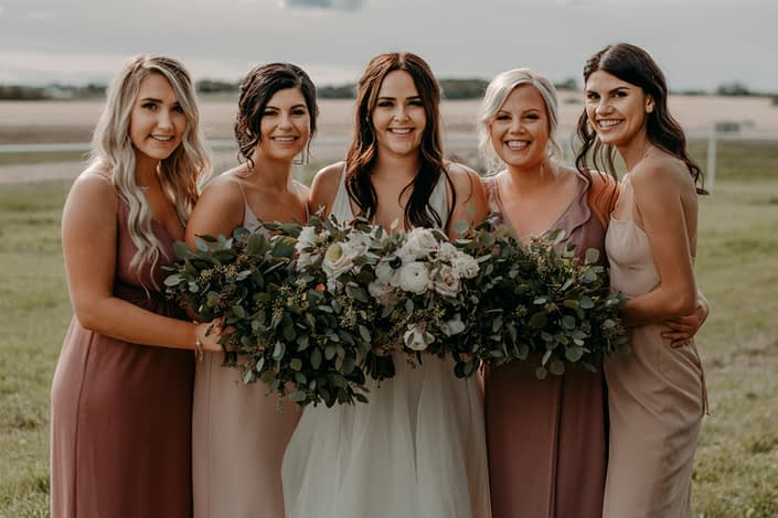 Erika and her bridesmaids - the bridesmaids are wearing mauve dresses and carrying fresh mixed eucalyptus bouquets and the bride is wearing a white bridal gown and carrying a white, ivory and blush bouquet featuring quicksand roses, panda anemones, white ranunculus and white lisianthus with eucalyptus greenery.