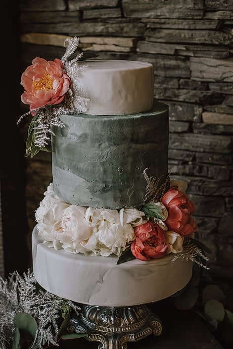Tiered cake by Stella Bean Sweets for the Canyon Ski Resort Open House 2019. Cake on a marble stand and is adorned with coral charm and white peonies with silver painted plumosa.