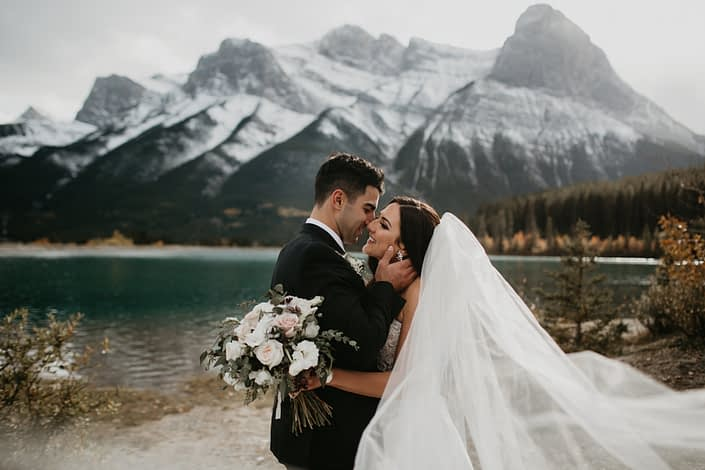 Brittany and Briggs with blush and ivory bridal bouquet in front of the Canmore mountains