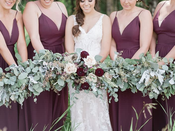 Bride, Santaya, and bridesmaids bouquets; bridesmaids carrying greenery bouquets designed with dusty miller, eucalyptus and olive branches; bridal bouquet designed with quicksand roses, burgundy dahlias, astilbe, astrantia, brown lisianthus and matching greenery.