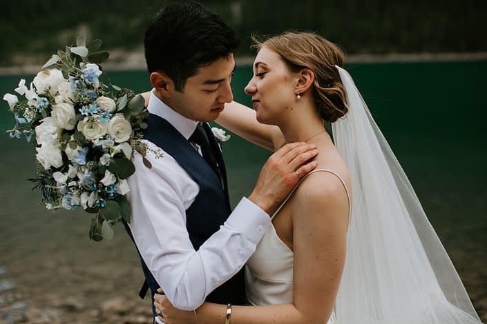bride and groom with white and blue bridal bouquet