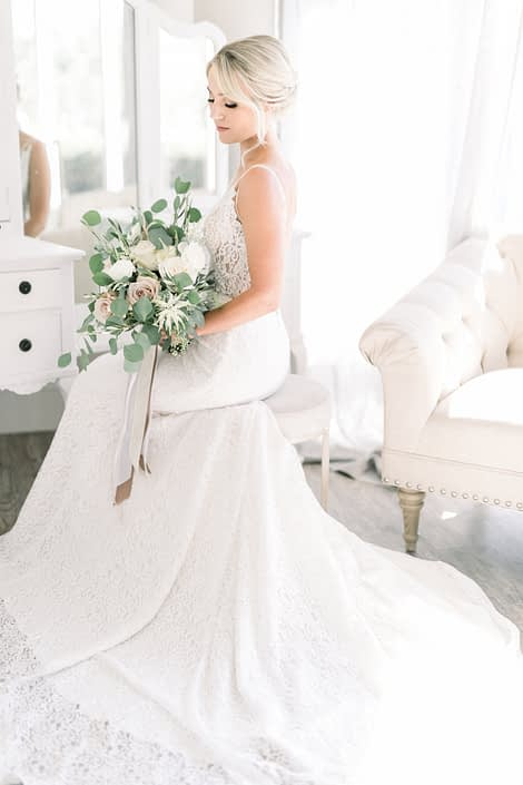 Kayla and Joel's Timeless White Wedding - Bride wearing a lace gown and holding an elegant bouquet featuring white o'hara garden roses, white ranunculus, quicksand roses, white astilbe, olive branches and a mixed variety of fresh eucalyptus.