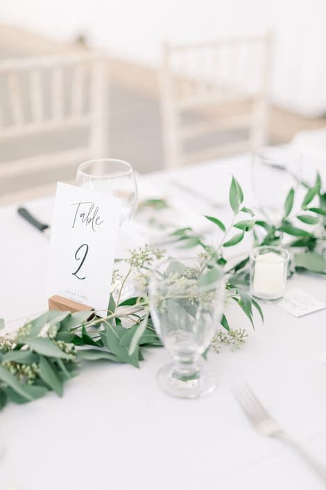 Simple elegant table cards and fresh greenery garland centrepieces of eucalyptus and Italian ruscus.