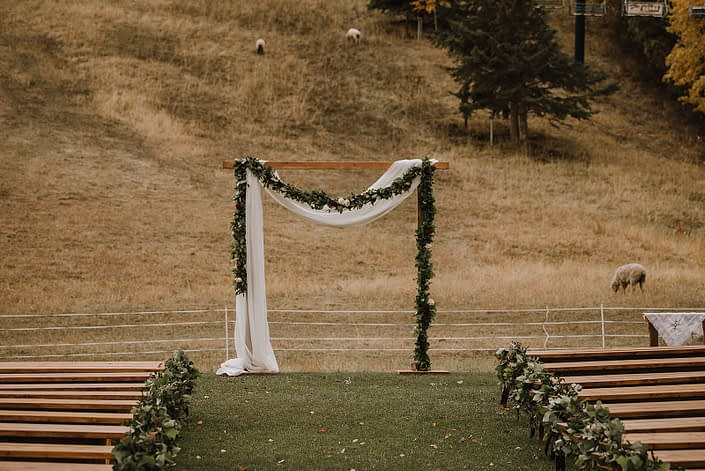 Cermeony site at CAnyon Ski resort decorated with frsh greenery garland and voile draping over the rustic wooden archway with sheep in the background