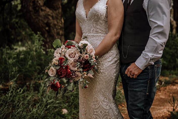 Bride and groom standing together with a rustic red and blush bridal bouquet made of red charm peony, quicksand roses, blush spray roses, light pink astilbe, burgundy astrantia and eucalyptus greenery.