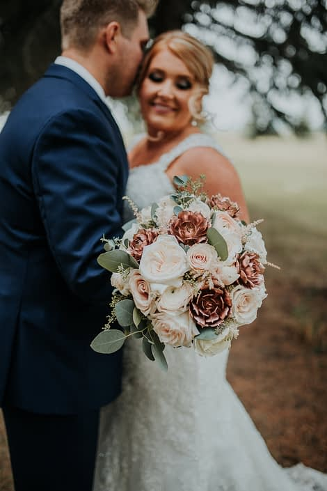 Close up of bridal bouquet made with rose gold succulents white ohara garden roses and blush quicksand roses and eucalyptus held by bride and groom in navy suit