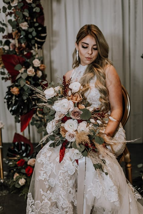 Cambridge Bridal Show 2020 - model wearing lace bridal gown holding bridal bouquet made of pampas grass, red and blush roses, ranunculus, and eucalyptus greenery tied with trailing ribbon. She is surrounded by dramatic tall vertical arrangements made of black monstera leaves, red and metallic dyed Anahaw palm leaves, red and blush roses and eucalyptus greenery.