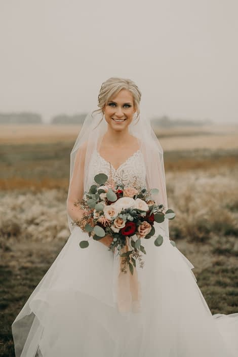 bridal portrait of bride with veil and lace dress with blush bouquet with quicksand roses and white o'hara garden roses and pink astilbe and red roses and blue eryngium and silver dollar eucalyptus in a prairie field