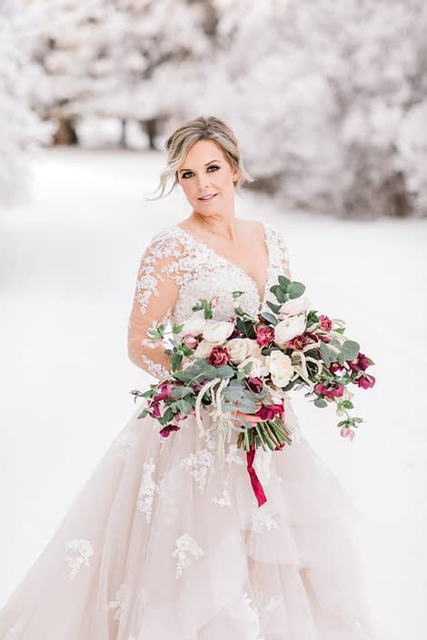 Winter bride standing in a wonderland of snow with blush and burgundy bridal bouquet