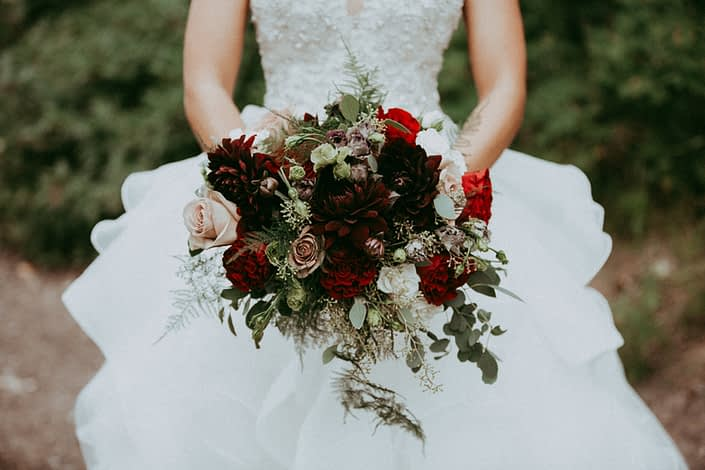Burgundy, red and mauve bridal bouquet designed with hearts garden roses, amnesia roses, burgundy dahlias, black pearl lisianthus, ivory spray roses, plumosa and eucalyptus
