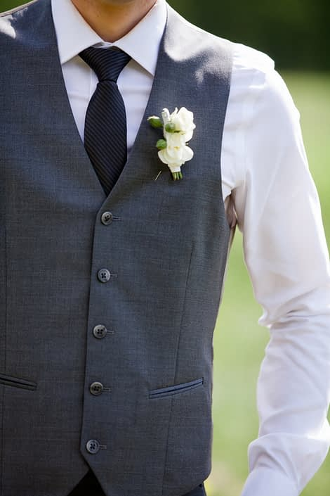 Groom wearing a grey vest with a ivory spray rose boutonniere accented with greenery.