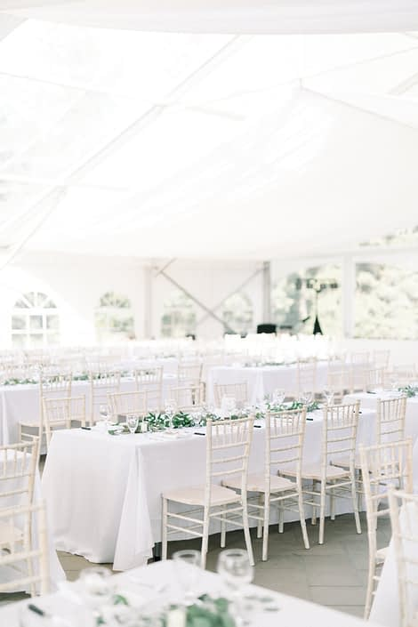Simple white reception venue accented by garlands of fresh greenery including eucalyptus and Italian ruscus.