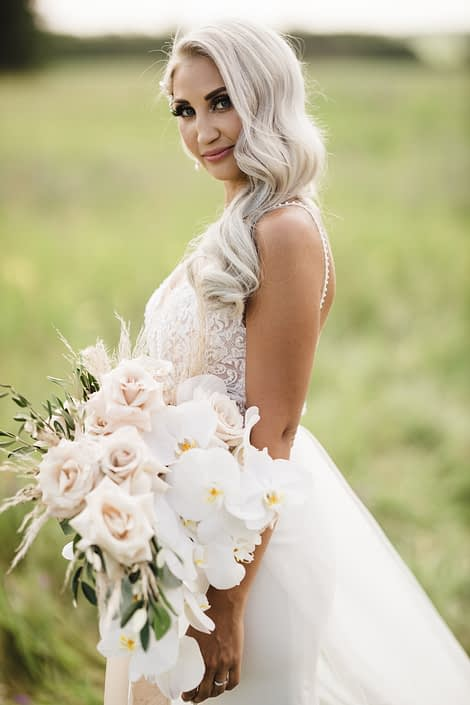 Boho Glam Bride with cascading bouquet featuring Phalenopsis orchids, quicksand roses, pampas grass, olive branches and silver dollar eucalyptus.