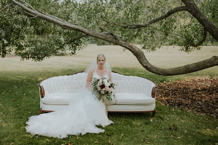 bride sitting in a park under an old tree on an ivory sofa holding a bridal bouquet in blush, white and burgundy with eucalyptus greenery