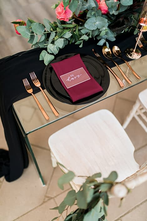 clear glass sweetheart table with black table runner and black place settings and gold cutlery with floral arrangements of cinerea eucalyptus
