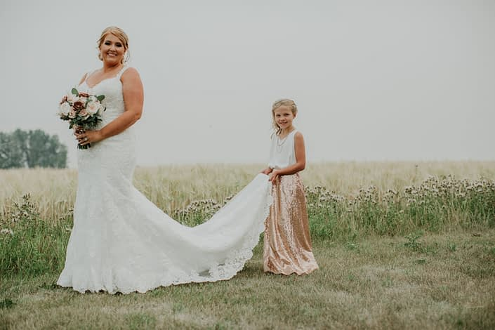 Bride and flowergirl in a wheat field with rose gold sequin skirt and bouquet of ivory and blush roses and rose gold succulents and eucalyptus