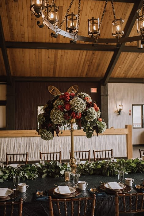 A tall centerpiece designed atop a gold candleabra and eucalytus table runner placed along a live edge table at Canyon Ski Resort long table dinner
