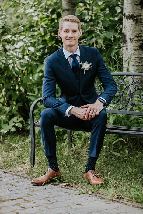 Groom, Ryley, with classic white ranunculus boutonniere