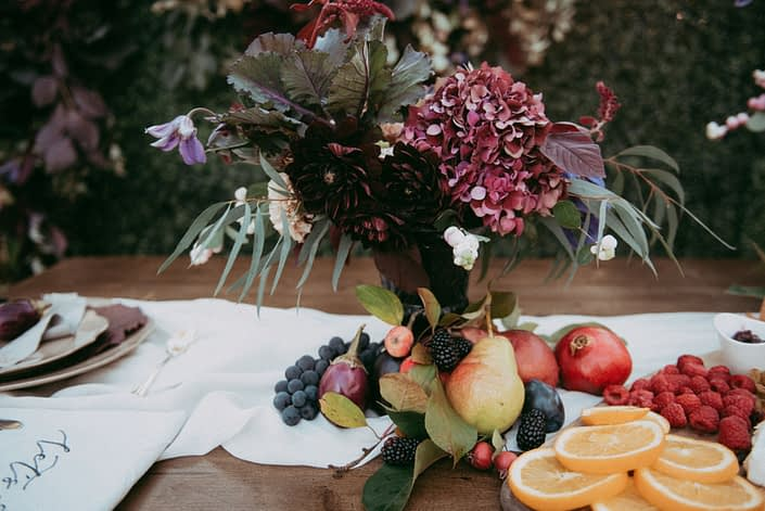 Fresh fruit on harvest table with charcuterie board and floral arrangement of burgundy dahlia, hydrangea and kale with purlpe clematis accents and snowberry