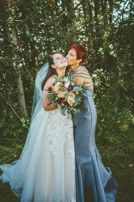 Bride and mother of the bride with mustard yellow bridal bouquet accented by ivory and burgundy flowers.