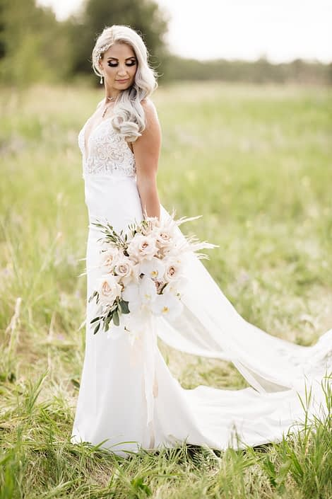 Sandra standing with boho glam bridal bouquet featuring phalenopsis orchids, quicksand roses, pampas grass, olive branches and silver dollar eucalyptus.