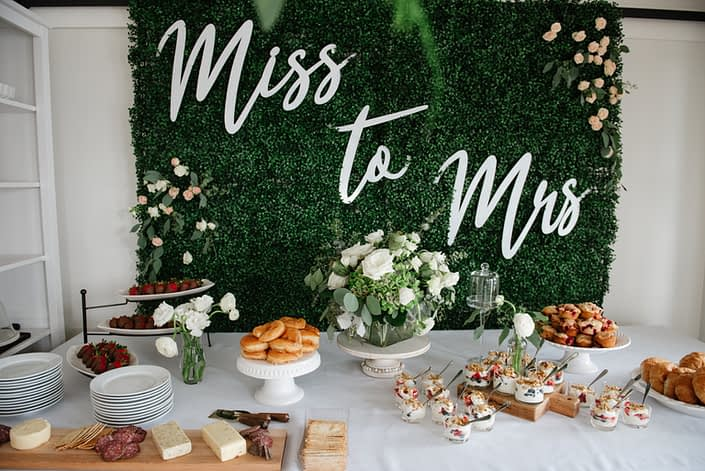 Boxwood backdrop for miss to mrs bridal shower overlooking dessert table with donuts, muffins ad charcuterie board and floral arrangements in blush, white and greenery