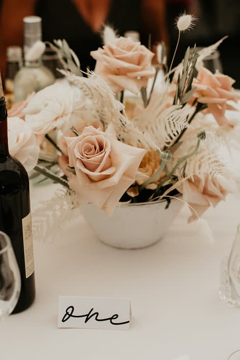 Rustic Boho Centrepieces designed with quicksand roses, blush ranunculus, bunny tail, and bleached bracken fern with olive branches
