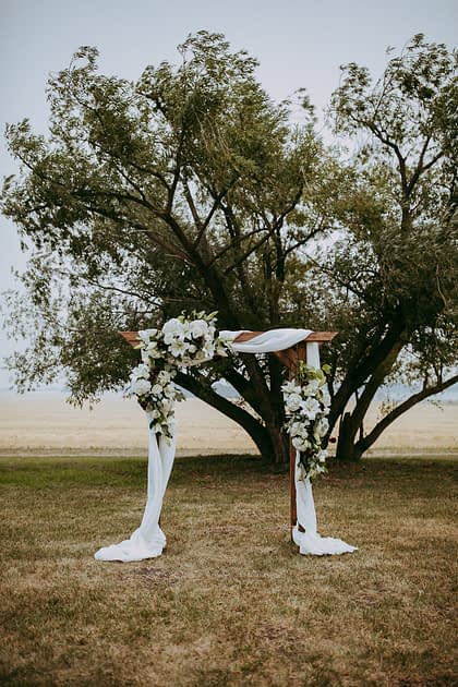 Archway with voile drapery and fresh white floral arrangments on rustic archway in a wheat field with tree backdrop