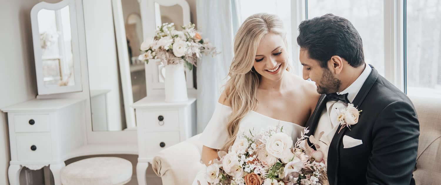 Bride and groom looking at pink and white and rose gold bridal bouquet designed with roses, ranunculus and hellebores