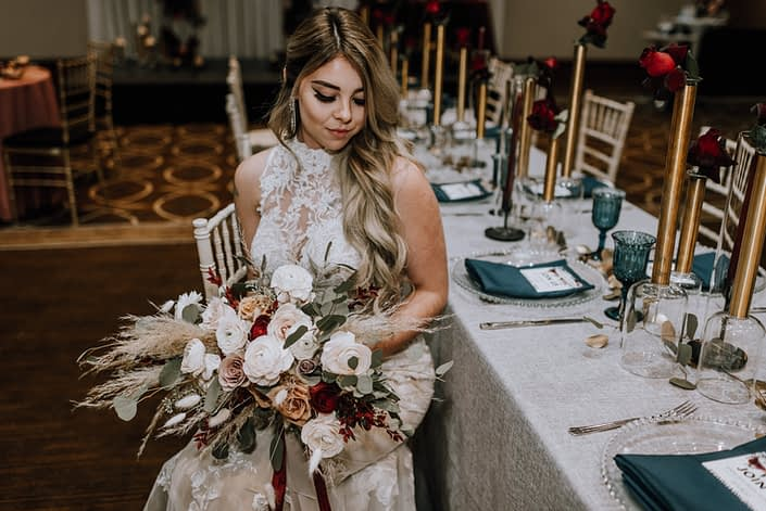 Cambridge Bridal Show 2020 - Bride wearing lace dress and holding bridal bouquet of pampas grass, blush and red roses, blush ranunculus and eucalyptus greenery with trailing ribbon.