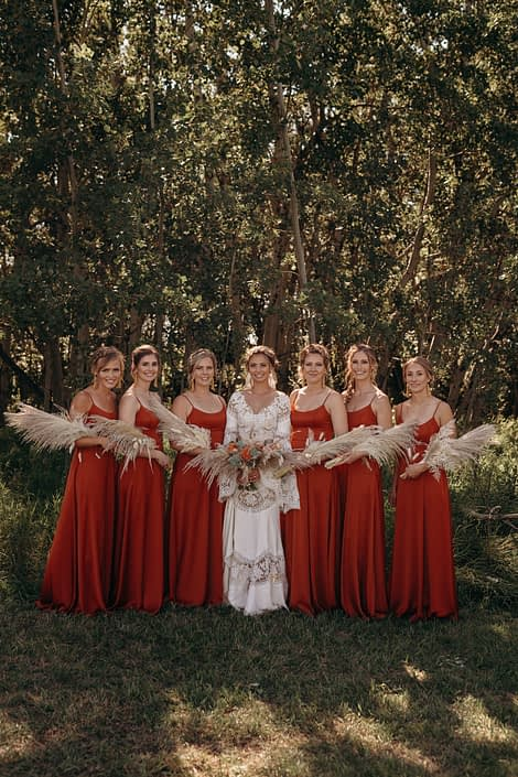 Bride and orange bridesmaids; boho bouquets made of pampas grass, bleached bracken fern, bunny tails and orange flowers
