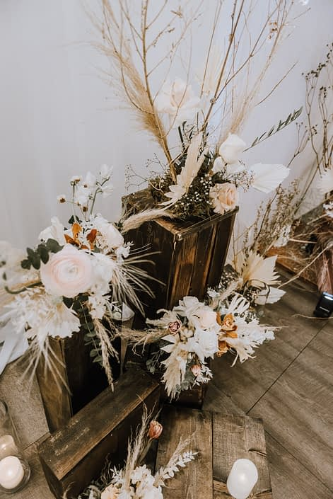 Arrangements on wooden crates at the Down the Aisle Wedding Show 2020 designed with dried leaves and branches, white playa blanca roses, orchids, pale pink ranunculus and pampas grass.
