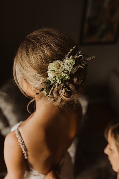 Vintage inspired hair flowers made with white lisianthus, spray roses and astilbe accented by grey toned greenery.