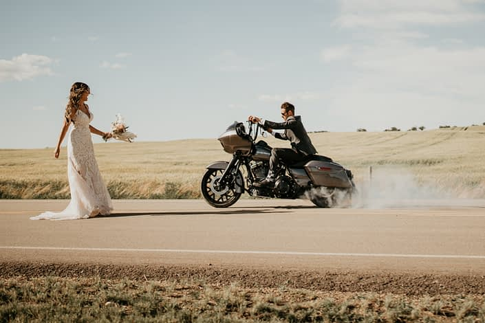 Bride and groom on a highway with motorcycle and rustic boho bridal bouquet
