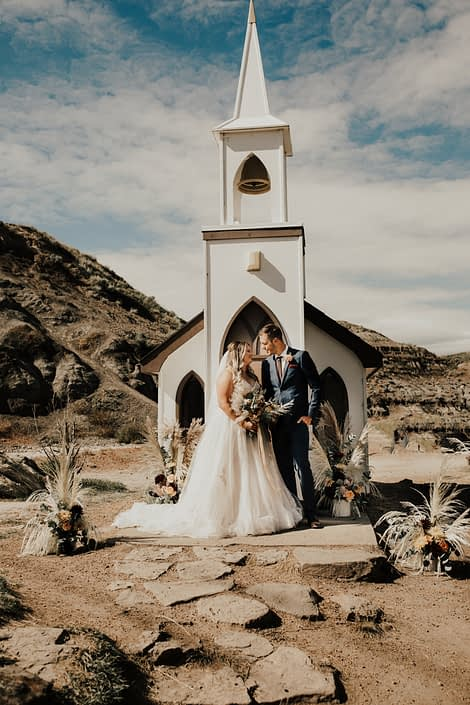Bride and groom in front of a church in Drumheller with boho floral arrangements