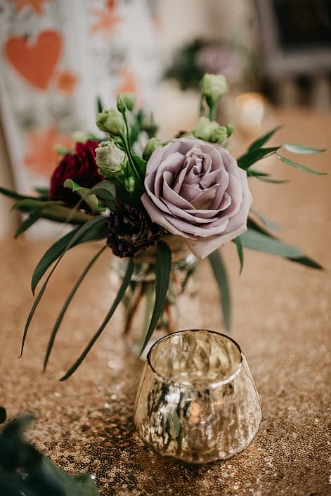 Rustic Boho Chic Wedding - Small arrangement made of a mauve rose, red rose and plum scabiosa on a gold sequin covered table.