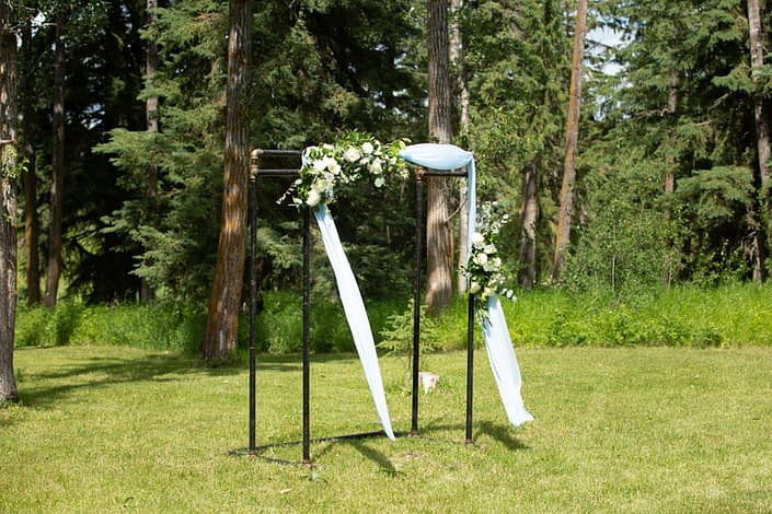 Archway arrangements designed with blue and white flowers on a pipe archway with blue drapery