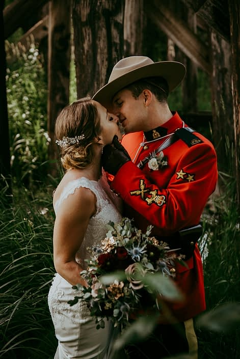 Tanya and Sean's RCMP Wedding - bride and groom kissing with bridal bouquet designed with black baccara roses, burgundy dahlias, navy eryngium, amnesia roses, rose gold succulents, and eucalyptus greenery