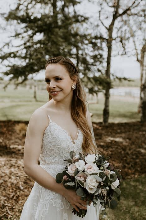 Rustic Elegance bride, Emily, wearing white lace bridal gown with vintage and rustic vibes, holding a blush, white and burgundy bridal bouquet