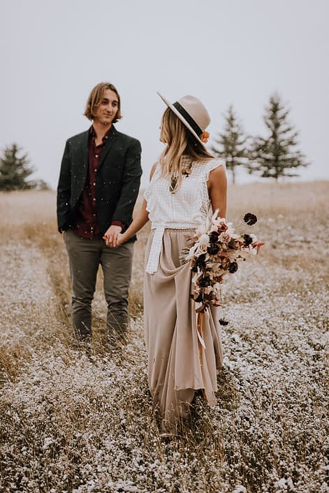 Couple walking through a field with falling snow and a neutral fall bouquet designed with plum scabiosa, roses, sweet peas, bunny tails and fall foliage