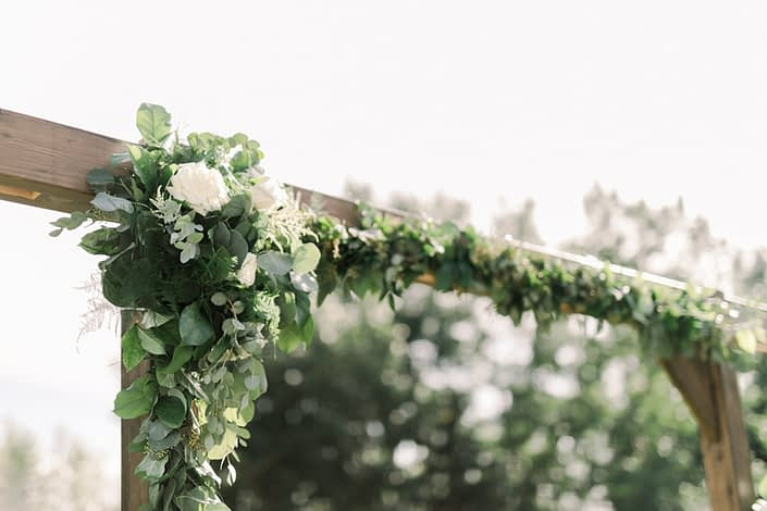 Wooden archway arrangement designed with white Tibet roses, a mixed variety of fresh eucalyptus, salal, italian ruscus and plumosa.