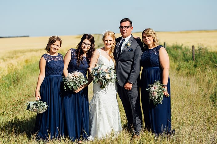 Bride and groom with bridesmaids near a field of wheat with bouquets made of blush roses, blue delphiniums, succulents, babies breath and eucalyptus greenery.