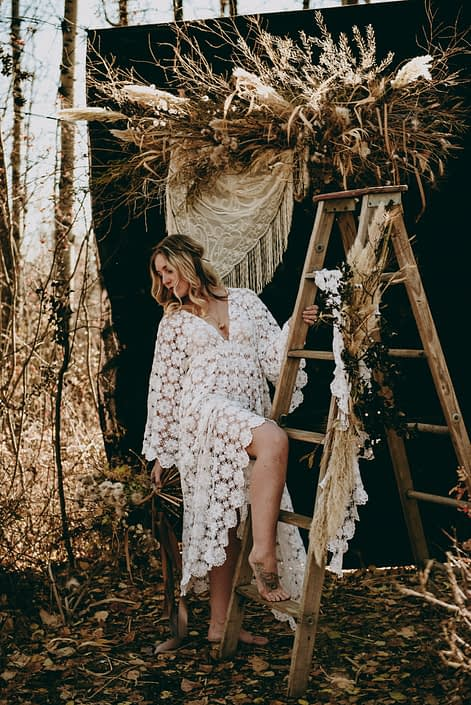 fall boho bride in the woods with rustic wooden ladder wearing a crocheted dress with a dried floral backdrop with crochet shawl accents