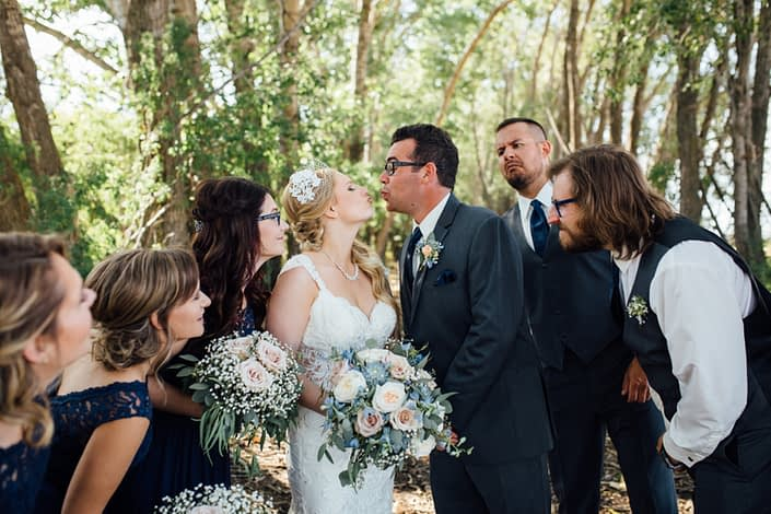 Bridal party watching as bride and groom are about to kiss; bridal bouquet featuring blue delphiniums, succulents, quicksand roses, white o'hara garden roses, babies breath and eucalyptus greenery.