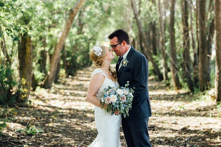 Kelsie and Kyle's Blush and Blue Vintage Barn Wedding - Bride and groom, Kelsie and Kyle, with blush and blue bridal bouquet and boutonniere featuring delphiniums, quicksand roses, white o'hara garden roses, gypsophila and a mixed variety of eucalyptus greenery.